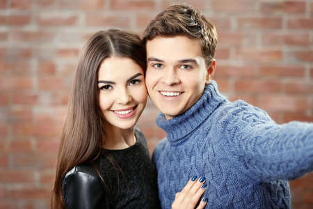 Teenager couple making photo by their self on brick wall background