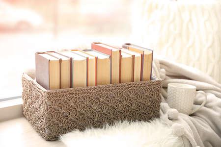 Pile of books in wicker box on windowsill, closeup Stock Photo