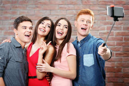 Teenager friends making photo by their self with mobile phone on brick wall background Stock Photo