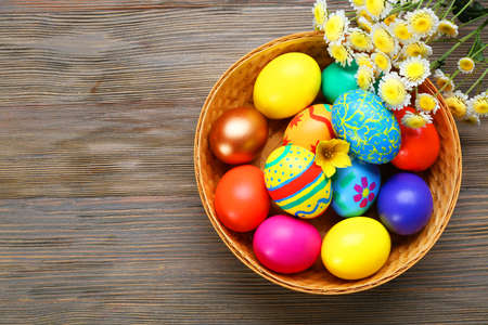 Easter eggs in basket with spring flowers on wooden background