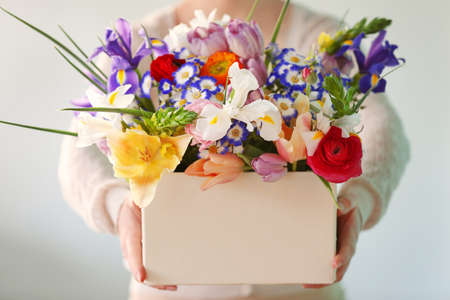 Woman holding a box of fresh flowers, close up