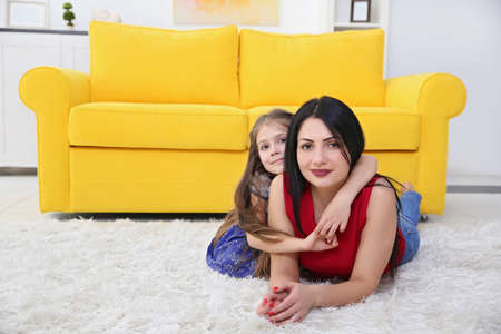 Mother and daughter lying on the carpet beside yellow sofa. Stock Photo