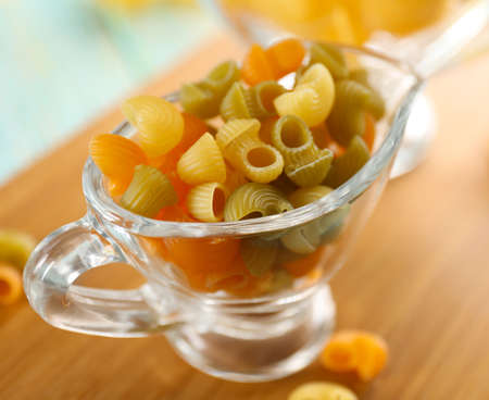 Raw pasta in glass saucer on wooden table closeup