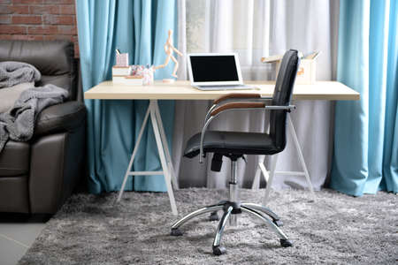 Workplace with table, laptop and office chair in living room Stock Photo