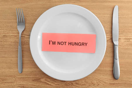 White plate with words Im not hungry on wooden background 스톡 콘텐츠
