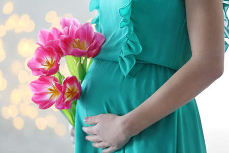 Pregnant woman in green dress holding pink tulips on glitter background Banque d'images