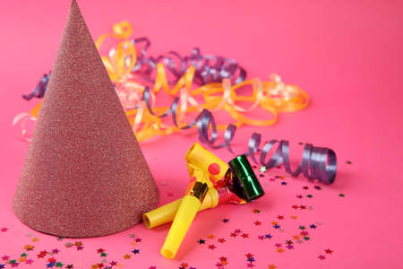 Birthday hat with serpentine streamer and noise makers on pink background