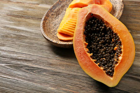 Halved papaya with slices on a wooden plate Stock Photo