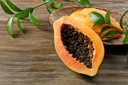 Halved papayas with leaves, close up Stock Photo