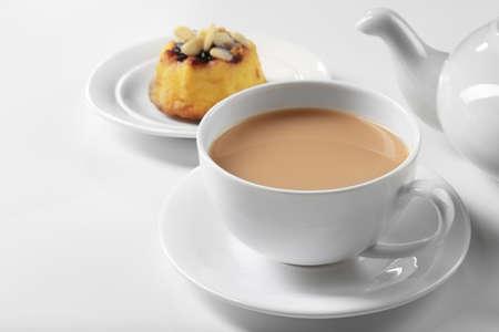 Milk tea with tea pot and a dessert on white background