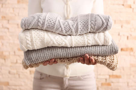 Woman holding knitted clothes, closeup Stockfoto