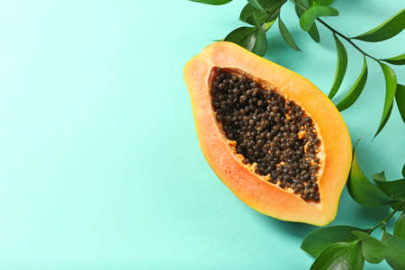 Halved papaya with leaves on blue background