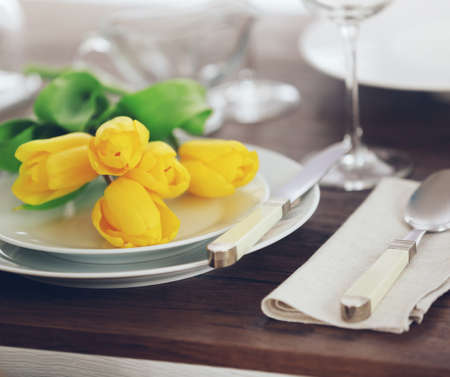Table setting with plates, cutlery and yellow tulips Stock Photo