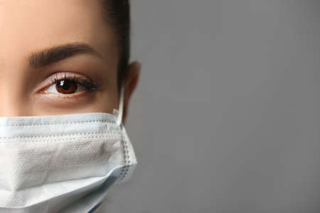 Young female doctor in medical mask on grey background