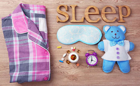 Word Sleep with pajamas, little toy and sleeping mask on a wooden background Stock Photo