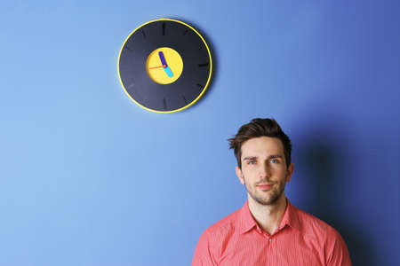 Man in a pink shirt standing beside a  big clock on blue wall
