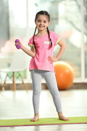 Little cute girl doing exercises with dumbbells on a mat indoor Foto de archivo