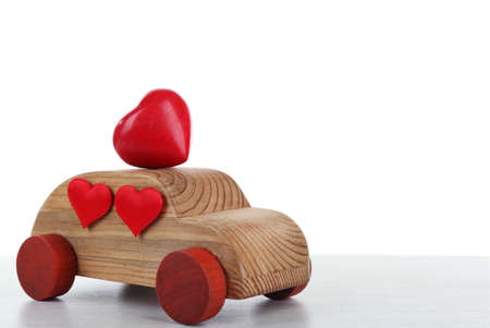 Wooden car with little red hearts on a white wooden table