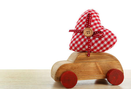 Wooden car with a red fabric heart on white wooden table