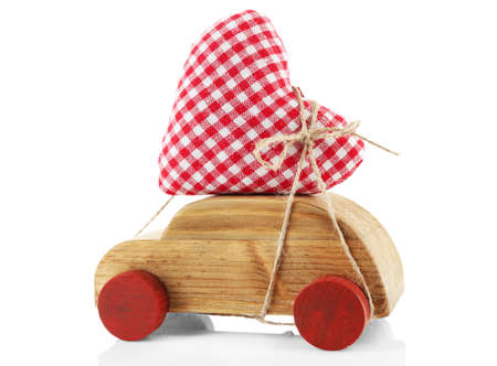 Wooden car with a red fabric heart  tied to it, isolated on white Stock Photo