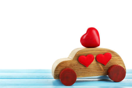 Wooden car with little red hearts on blue wooden table