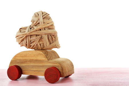 Wooden car with a wicker heart on pink wooden table Stock Photo