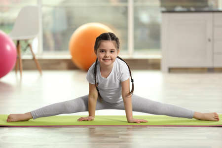Little cute girl stretching herself on a mat indoor