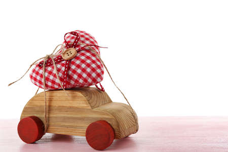 Wooden car with a red fabric heart  tied to it on pink wooden table Stock Photo