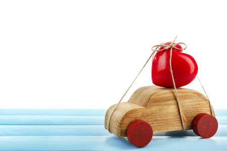 Wooden car with a red heart  tied to it on a blue wooden table over white background