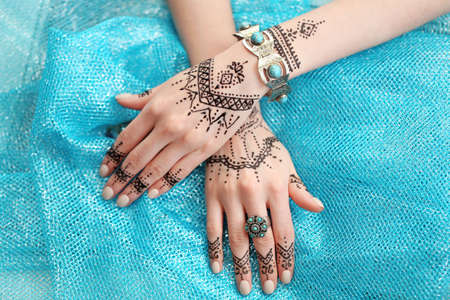 Weibliche Hände mit Henna Tattoo auf blauem Stoff Hintergrund
