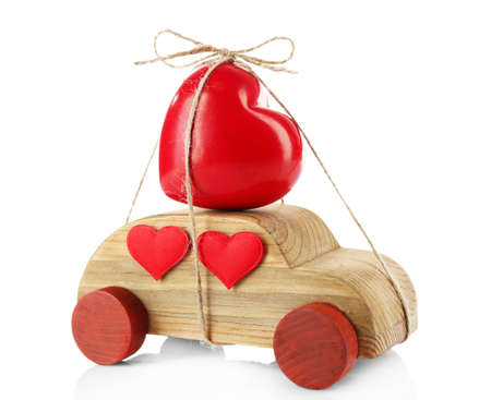 Wooden car with a red heart  tied to it, isolated on white Stock Photo