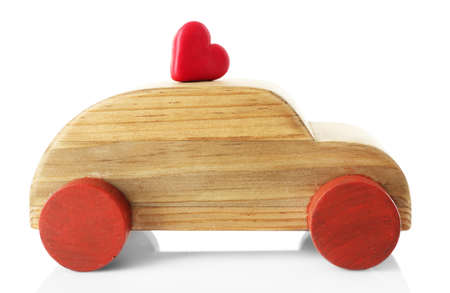 Wooden car with a little red heart figure isolated on white
