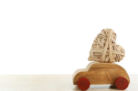 Wooden car with a wicker heart on a white wooden table