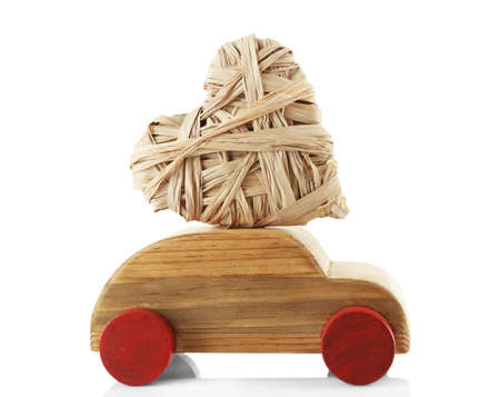 Wooden car with a wicker heart, isolated on white