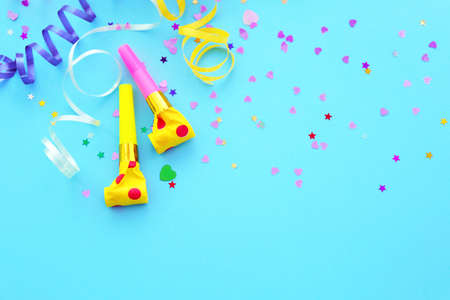 Blowers, streamers and confetti on blue background Stock Photo