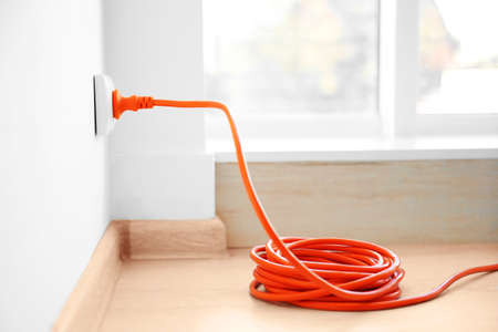 Orange extension into power outlet indoors
