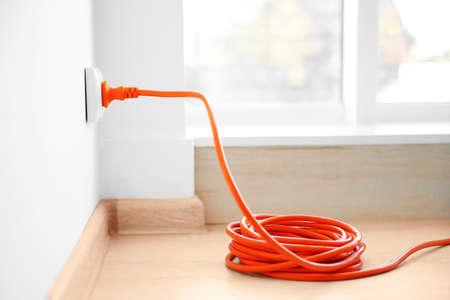 Pomarańczowe rozszerzenie do gniazdka elektrycznego w pomieszczeniu