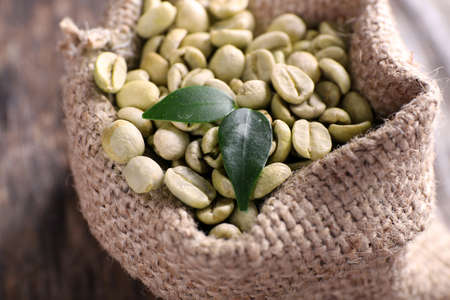 Green coffee beans in a bag  on wooden table