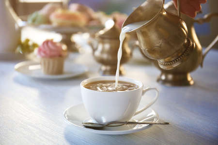Pouring milk into cup of tea on wooden table closeup