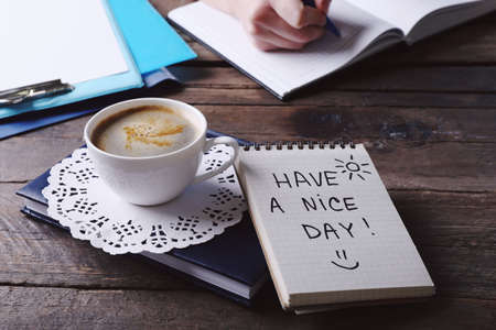 Female hands writing in notebook near cup of coffee and note HAVE A NICE DAY on wooden table closeup Foto de archivo