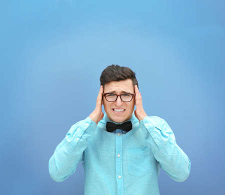 Attractive young man against light blue wall background