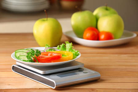 Plate of sliced fresh vegetables and digital kitchen scales on wooden table Stock Photo