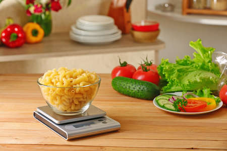Bowl of dry pasta and digital kitchen scales on wooden table Stock Photo
