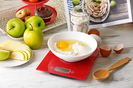 Bowl of raw egg and flour with digital kitchen scales on light wooden table
