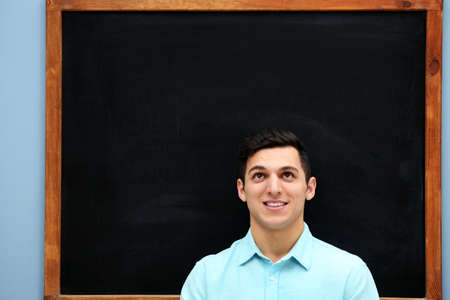 Attractive young man against blackboard.
