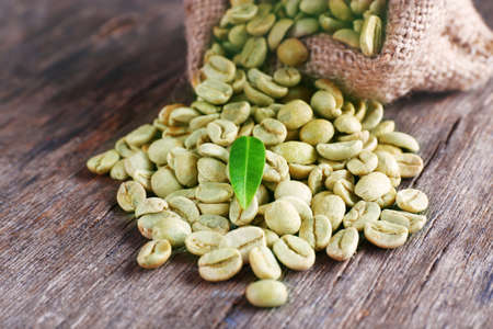 Green coffee beans with a leaf on  wooden table 版權商用圖片