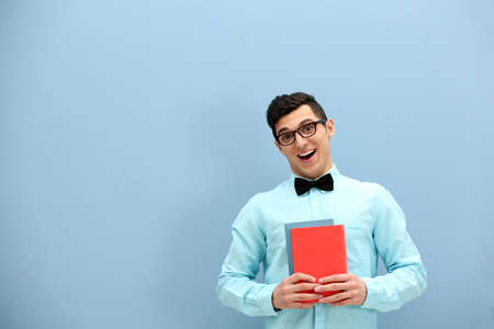 Attractive young man  against light blue wall