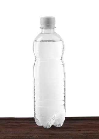 Mineral water in plastic bottle on wooden table on grey background Stock Photo