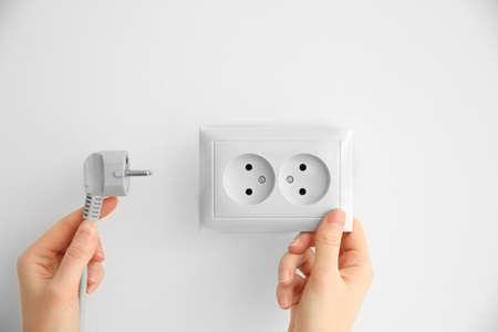 Womans hands holding power outlet and plug 版權商用圖片