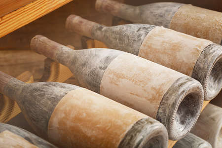 Old and dusty wine bottles in a wine cellar